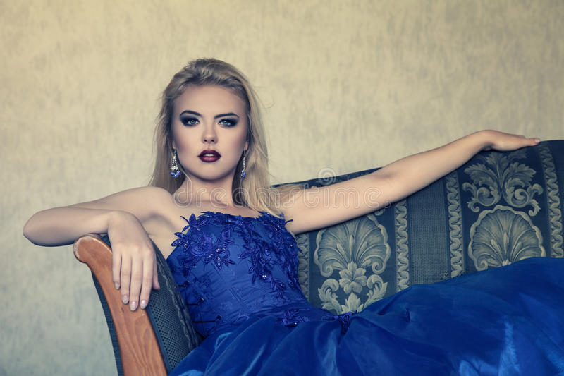 Young woman in luxurious blue dress. Sitting against dark background stock photos