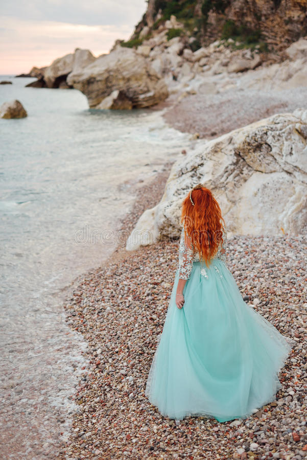 Young woman in a luxurious dress stands on the shore of the Adriatic Sea royalty free stock photography