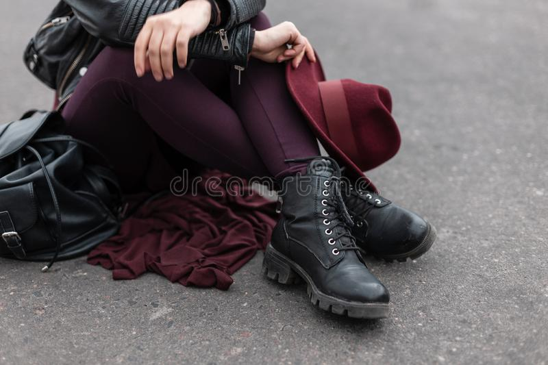 Young woman with a luxurious vintage purple hat in trendy trousers in leather fashionable black boots. Stylish women`s headdress. And shoes. Retro style. Close stock photography