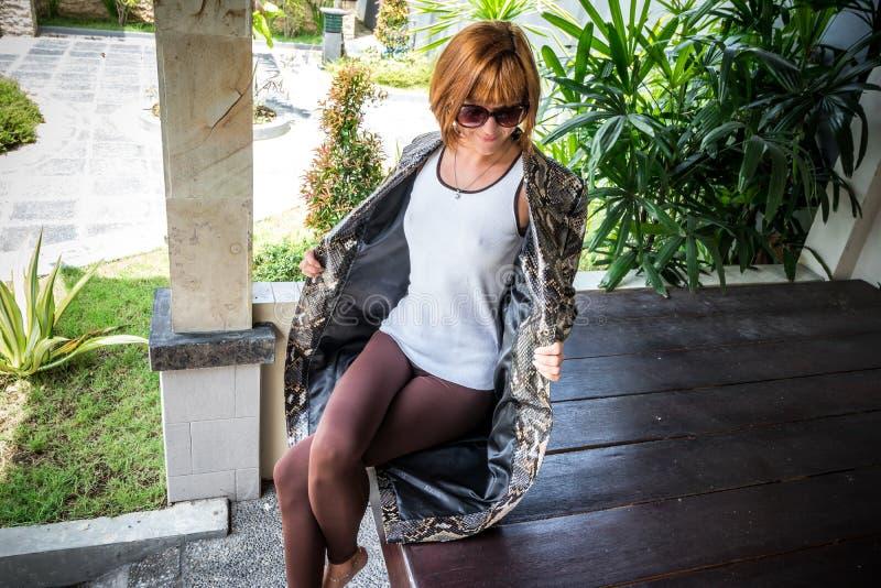 Young woman, luxury fashion snakeskin python cape cloak. Handmade snakeskin coat. royalty free stock photos
