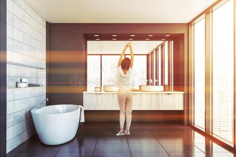 Young woman in luxury gray and wooden bathroom. Rear view of young woman standing in modern bathroom interior with gray and wooden tile walls, comfortable stock photography