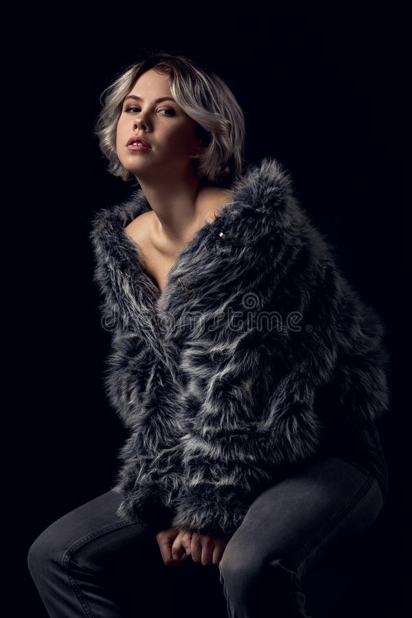 Young woman luxury style isolated on grey wall sitting on chair stock photos