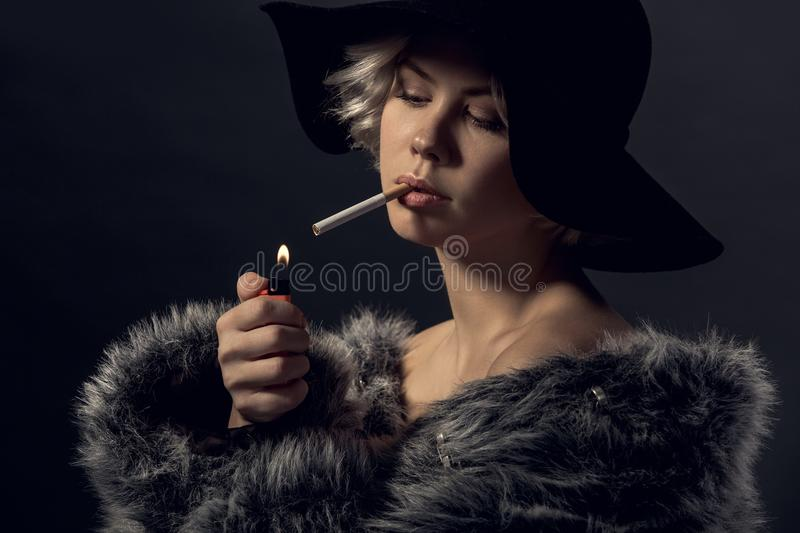 Young woman luxury style on grey wall smoker. Young woman luxury style wearing fur coat and hat lighting a cigarette smoker stock photo