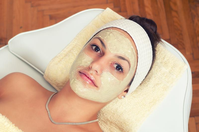 Young woman lying in beauty spa with facial mask on her face royalty free stock photo