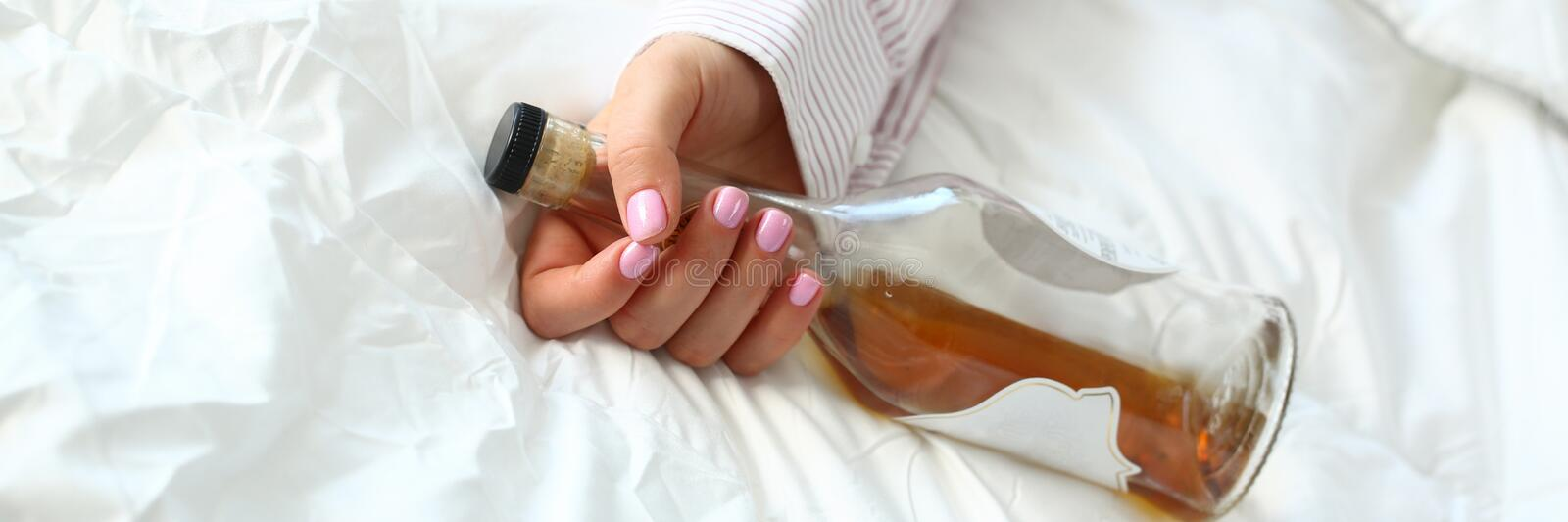 Young woman lying in bed deadly drunken. Holding near-empty bottle of booze. Female intoxicated with alcohol after tough night party. Alcoholism habitual stock images