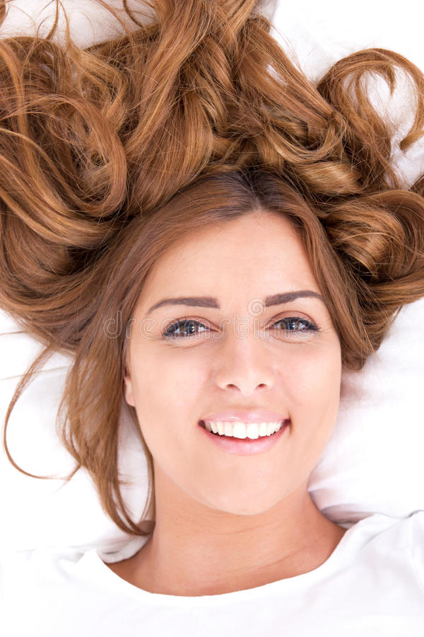 Young woman lying on bed with hair spread out. Closeup of happy pretty brunette young woman lying on bed with hair spread out, domestic atmosphere stock image
