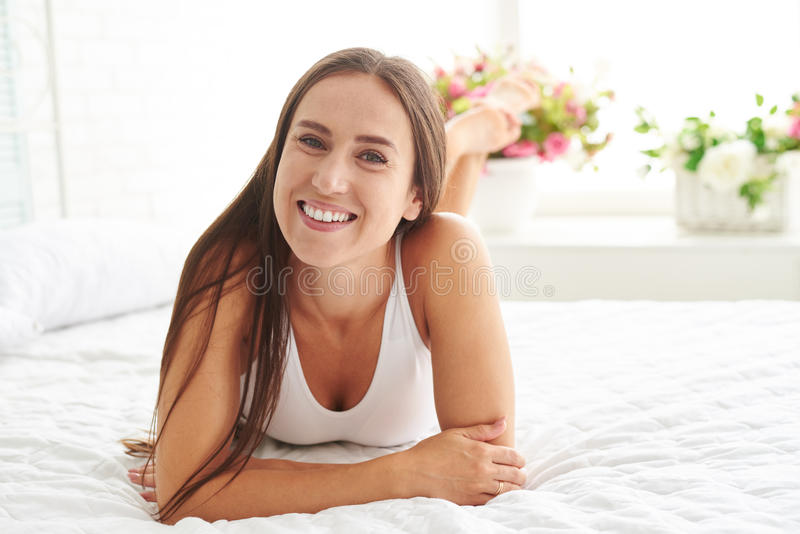 Young woman lying on bed with legs crossed royalty free stock photography