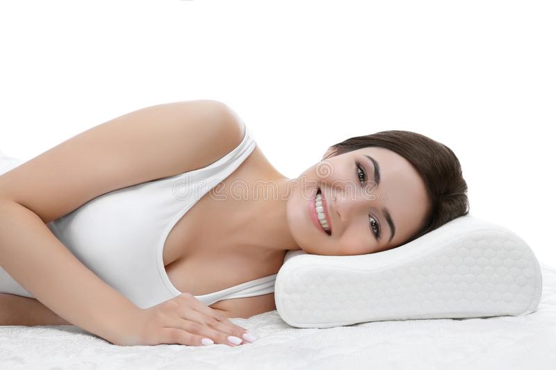 Young woman lying on bed with orthopedic pillow. Against white background. Healthy posture concept stock photography