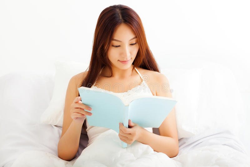 Young Woman lying in bed while reading a book. Beautiful young Woman lying in bed while reading a book stock photo