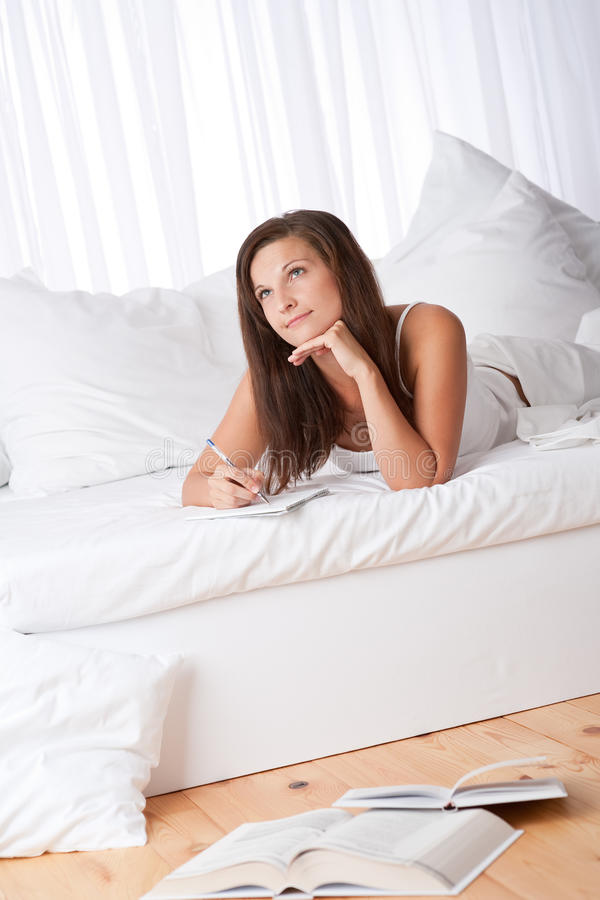 Young Woman Lying On Bed Writing Notes Royalty Free Stock Photos