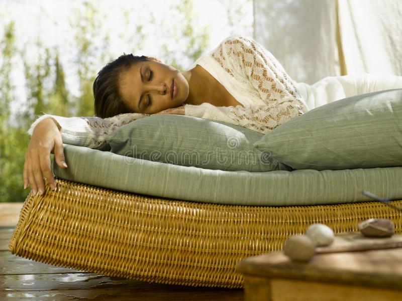 Young woman lying on a chaise lounge with her eyes closed royalty free stock photo