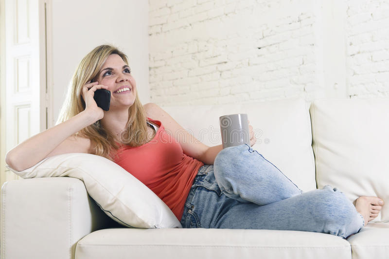 Young woman lying comfortable on home sofa couch talking on mobile phone smiling happy. Young attractive blond hair woman lying comfortable on home sofa couch stock photo