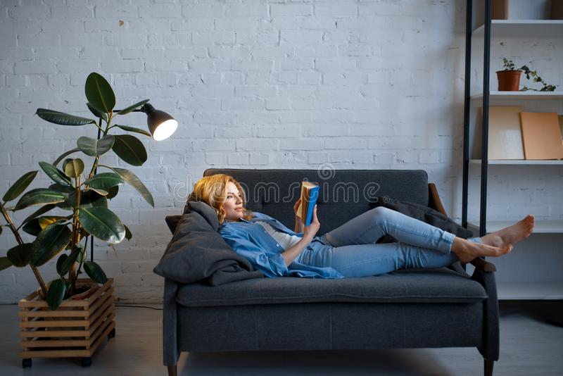 Young woman lying on cozy couch and reading a book stock photo