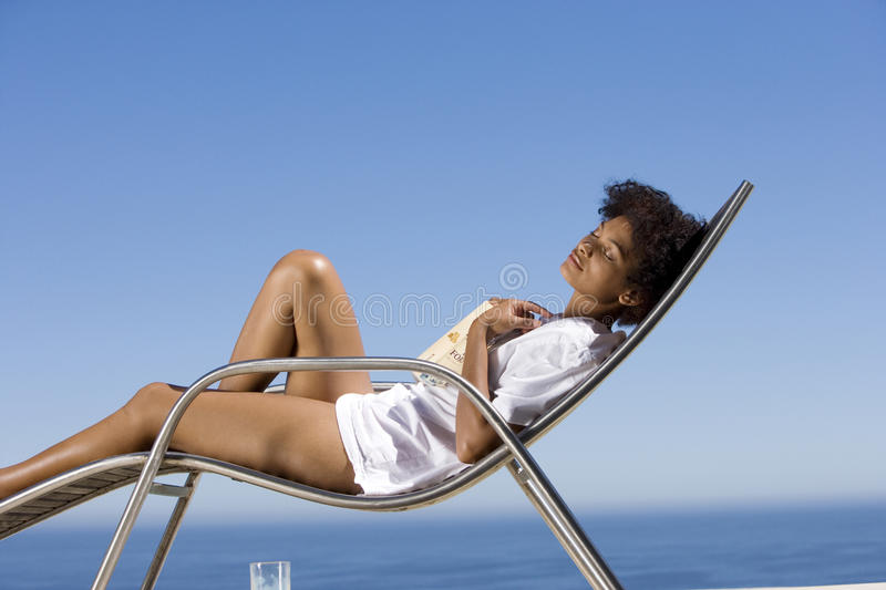 Young woman lying on deck chair with book by sea, eyes closed, side view stock images