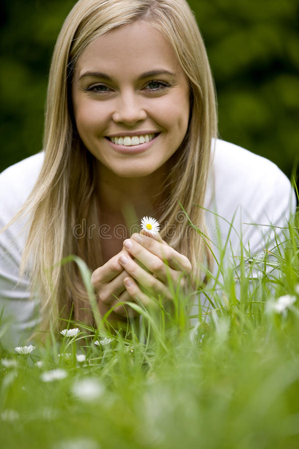 A young woman lying on the grass, holding a daisy stock photography