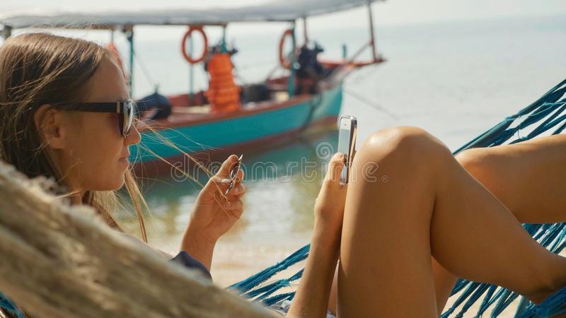 Young woman lying on hammock with smart phone and bank card at the sandy beach stock photo