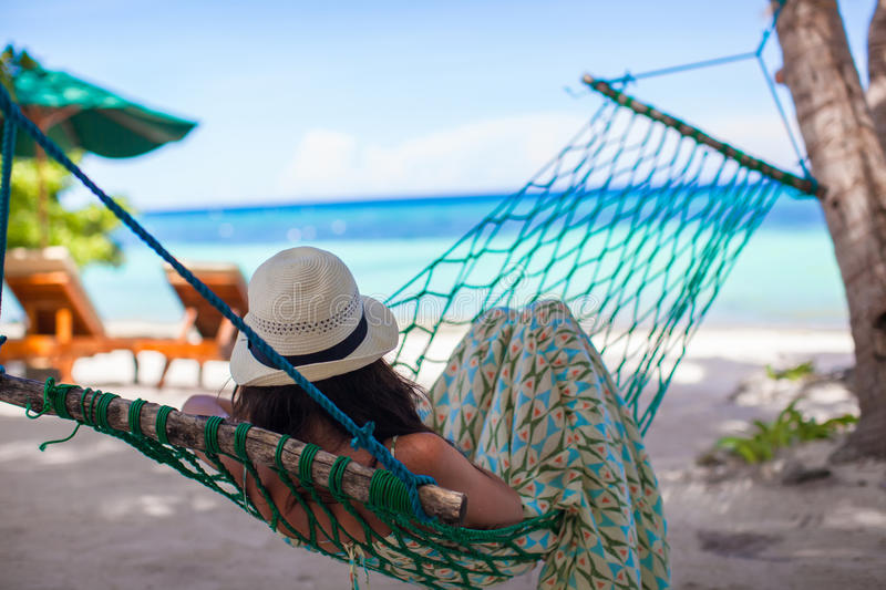 Young woman lying in the hammock on tropical beach. Happy young woman lying in the hammock on tropical beach royalty free stock photography