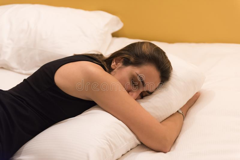 Girl sleeps in her bed. Young woman lying in her bed, hugging her white pillow and resting and sleeping in her warm bed royalty free stock images