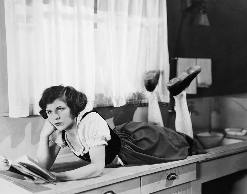 Young woman lying on a kitchen counter holding a book and thinking royalty free stock image