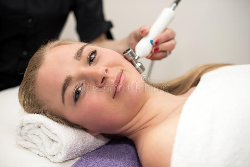 Young woman lying on massage table receiving face massage. Beaut stock photos