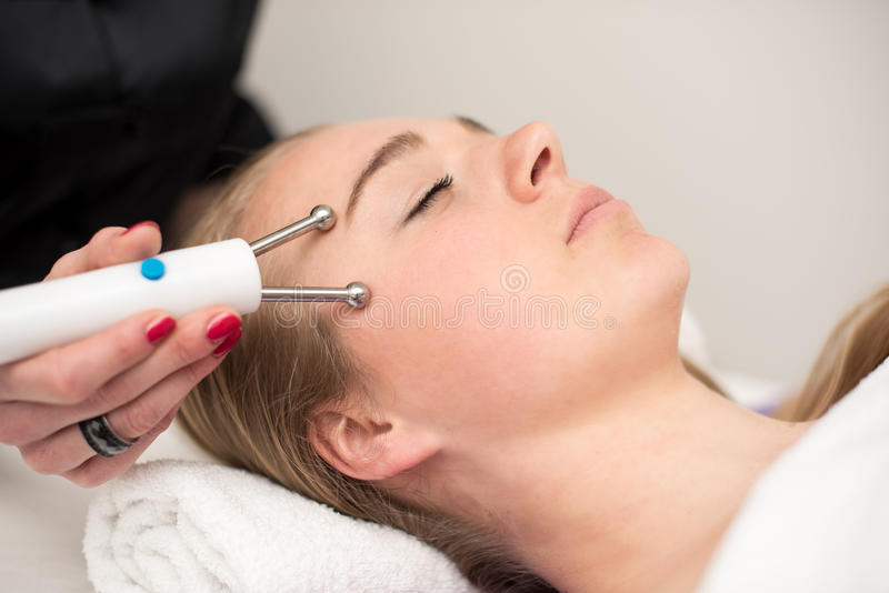 Young woman lying on massage table receiving face massage. Beaut royalty free stock image