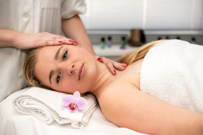 Young woman lying on massage table receiving face massage. stock photography