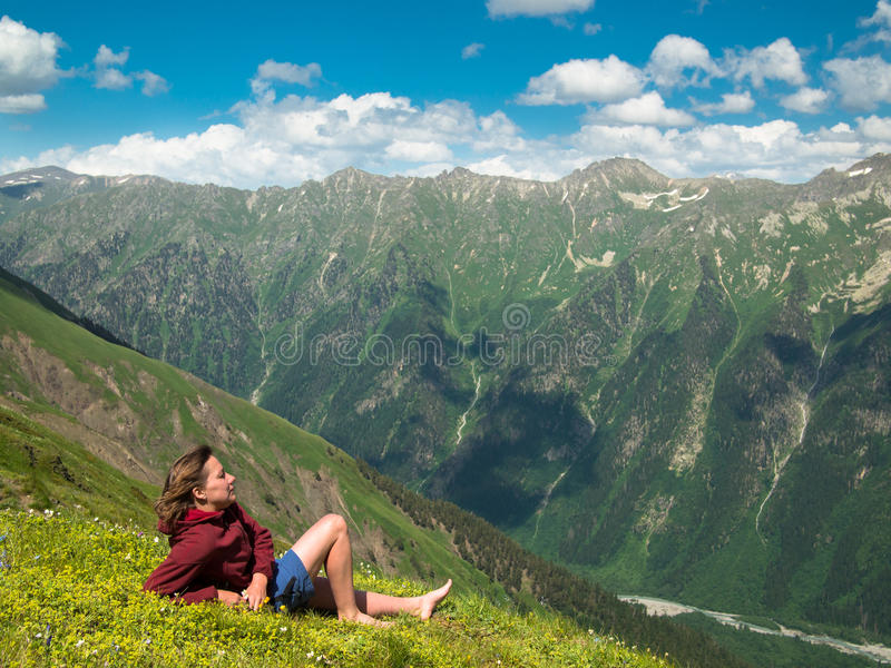 Young woman lying in a meadow with flowers in front of the North Caucasus mountain range stock image