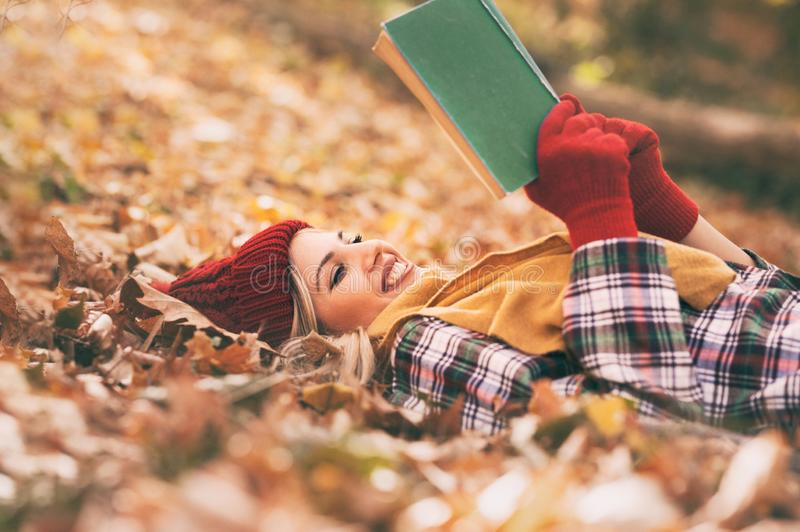 Young woman lying and reading her favorite book on  o autumn meadow stock images
