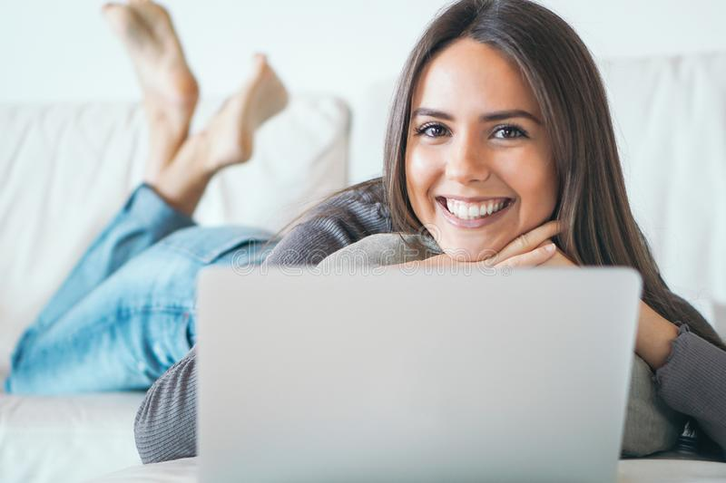 Young woman lying on sofa and using laptop at home - Happy girl surfing online with her computer while smiling at camera. Concept of people, technology and stock photos