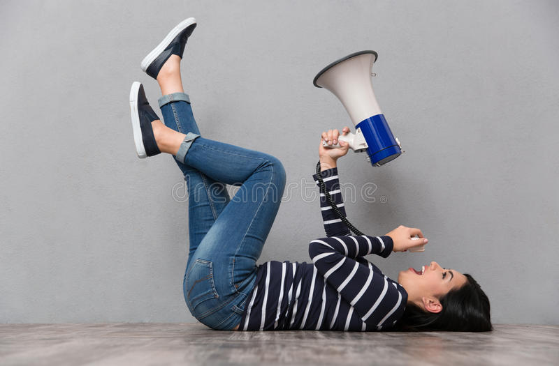 Young woman lying and speaking in megaphone stock photos
