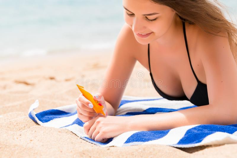 Young woman is lying on the towel at the beach and applying sunbclock from the tube on her hand.  royalty free stock image