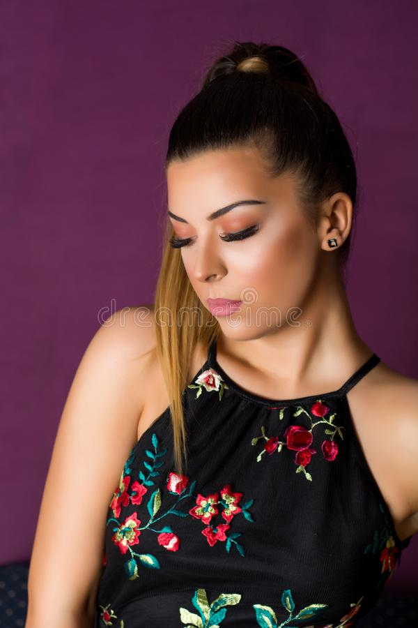 Woman with make up and silk eyelashes looking down posing on purple background. Young woman with make up and silk eyelashes looking down posing on purple royalty free stock images