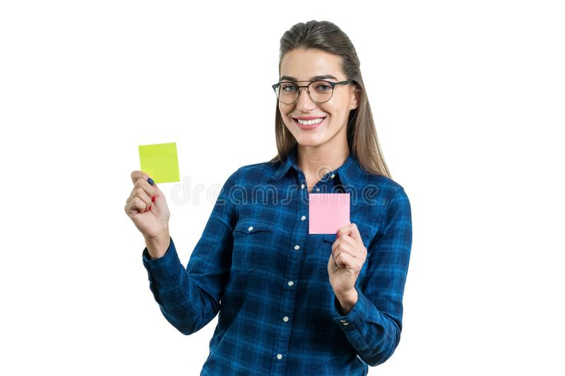 Young woman makes a choice. Photo is isolated, female holding two clean stickers of different colors, place for your text royalty free stock images