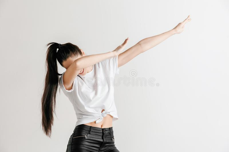 Young woman makes the dab movement with his arms on a gray background. Young woman makes a dab movement with arms on a gray background. Human emotions, facial royalty free stock photo