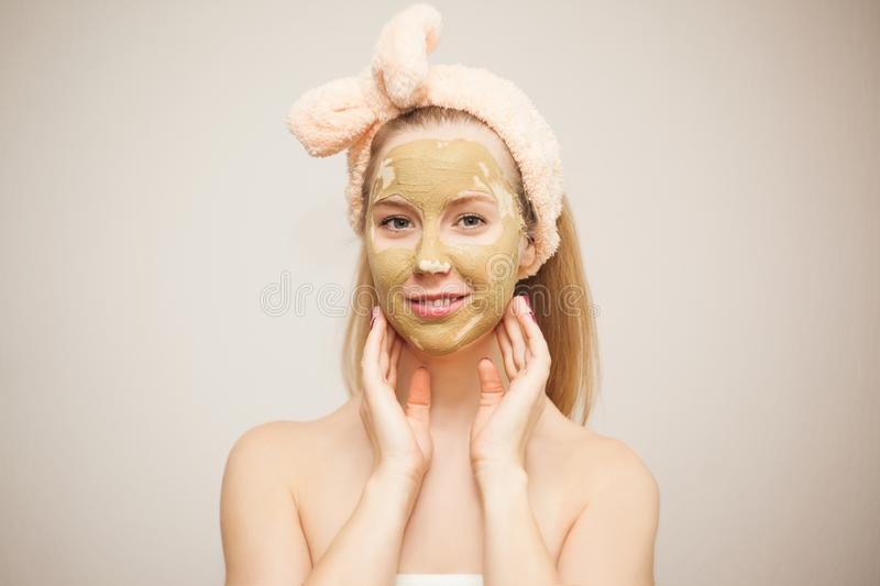 A young woman makes a face mask from clay. Cosmetic procedures. Home skin care stock photos