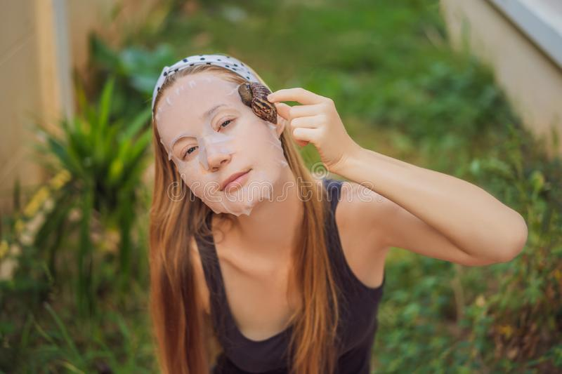 A young woman makes a face mask with snail mucus. Snail crawling on a face mask.  stock photo