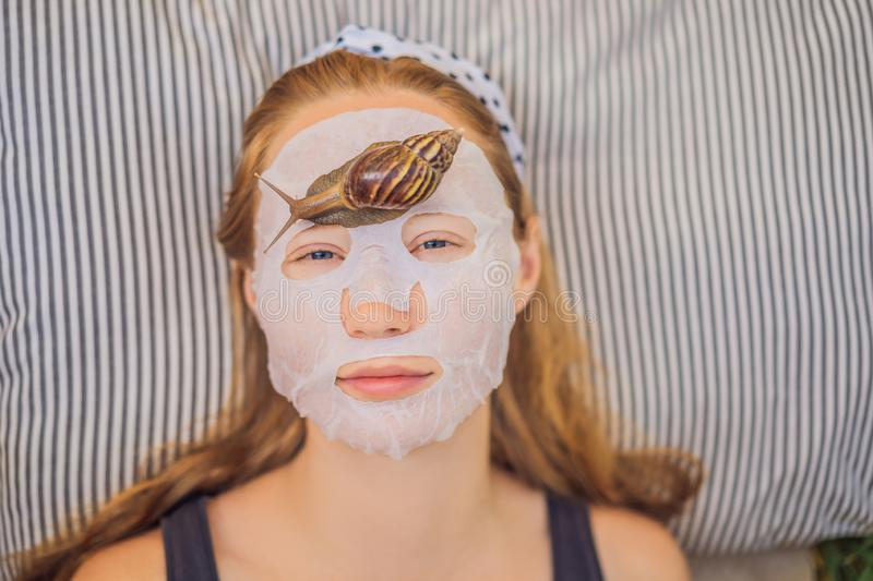 Young woman makes a face mask with snail mucus. Snail crawling on a face mask.  stock photos