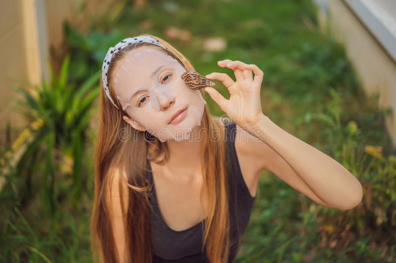 A young woman makes a face mask with snail mucus. Snail crawling on a face mask.  stock image