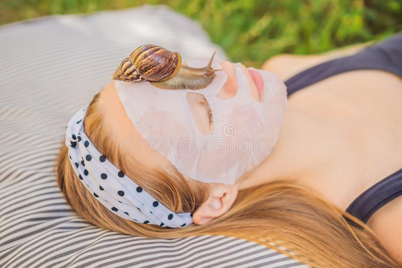 Young woman makes a face mask with snail mucus. Snail crawling on a face mask.  royalty free stock photo