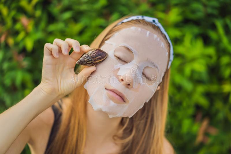 A young woman makes a face mask with snail mucus. Snail crawling on a face mask.  stock images