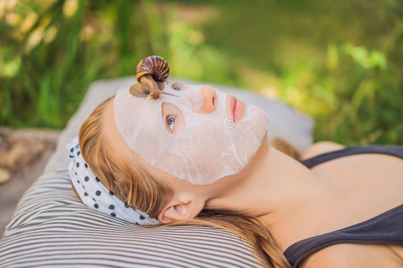 Young woman makes a face mask with snail mucus. Snail crawling on a face mask.  stock images
