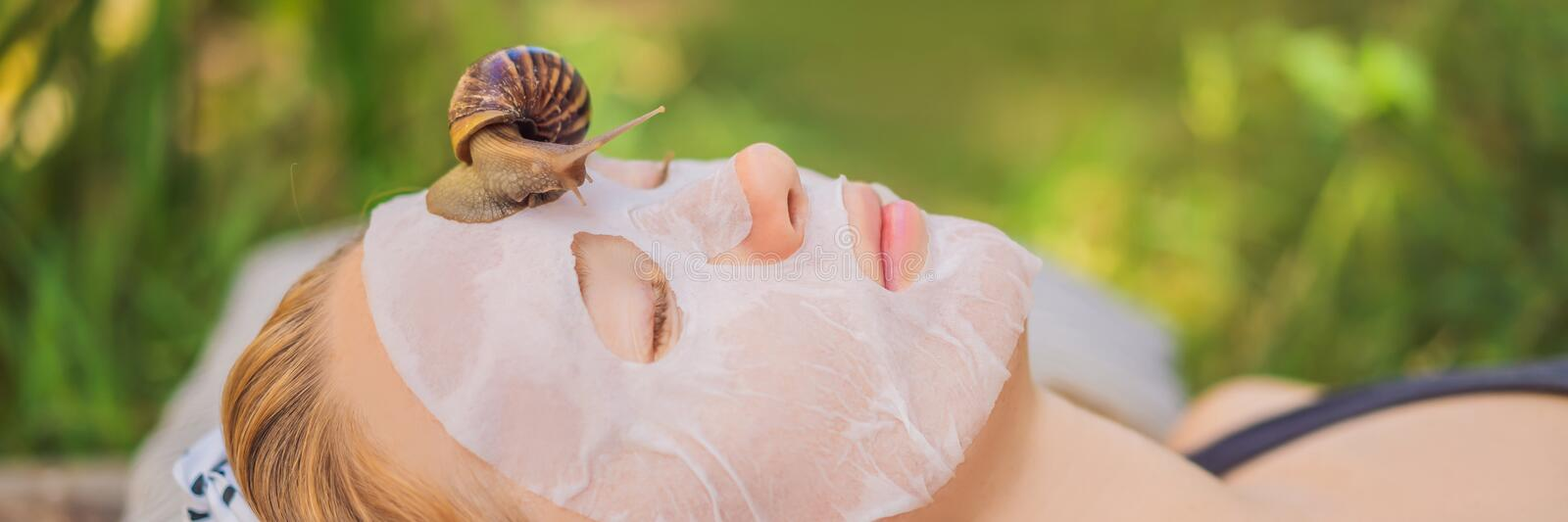 Young woman makes a face mask with snail mucus. Snail crawling on a face mask BANNER, LONG FORMAT. Young woman makes a face mask with snail mucus. Snail crawling stock photos