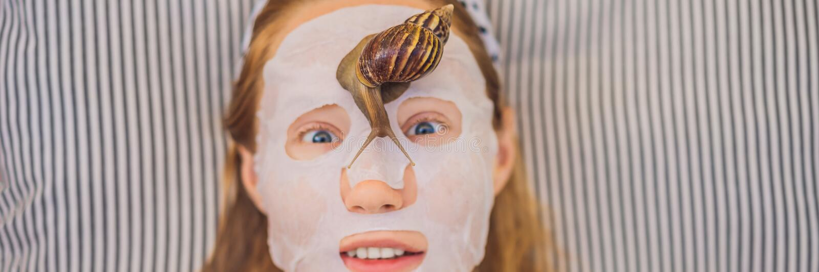 Young woman makes a face mask with snail mucus. Snail crawling on a face mask BANNER, LONG FORMAT. Young woman makes a face mask with snail mucus. Snail crawling stock images