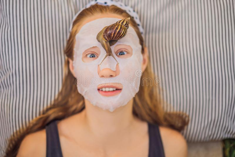 Young woman makes a face mask with snail mucus. Snail crawling on a face mask.  stock photography