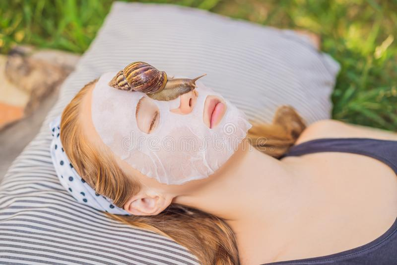 Young woman makes a face mask with snail mucus. Snail crawling on a face mask.  royalty free stock photography