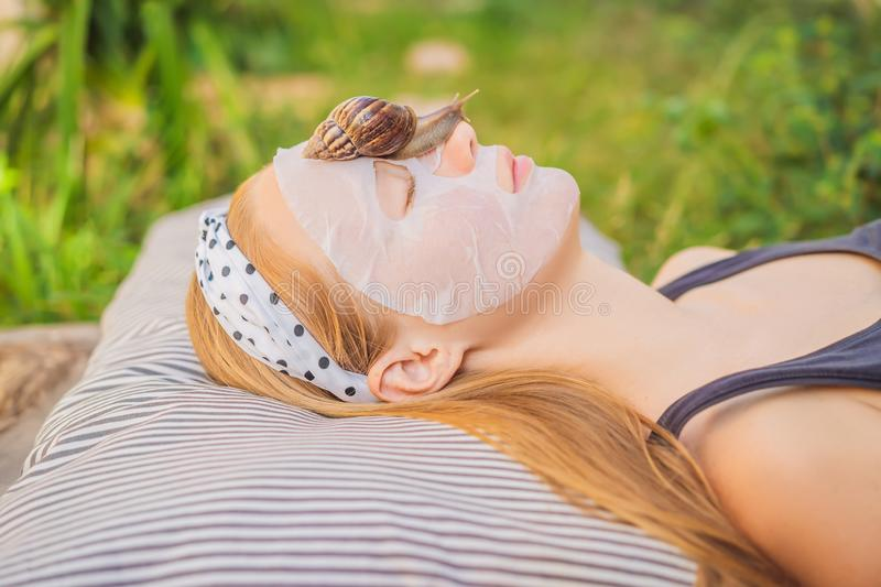 Young woman makes a face mask with snail mucus. Snail crawling on a face mask.  royalty free stock images