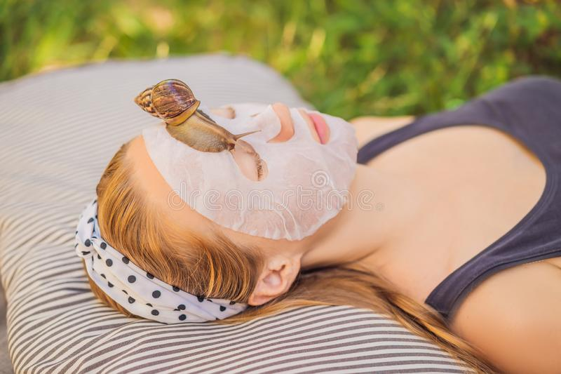Young woman makes a face mask with snail mucus. Snail crawling on a face mask.  royalty free stock photos