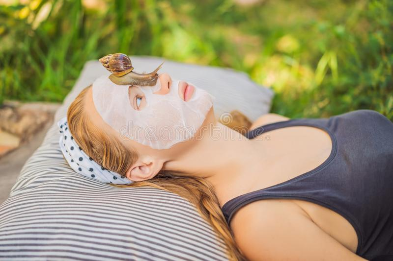 Young woman makes a face mask with snail mucus. Snail crawling on a face mask.  royalty free stock image