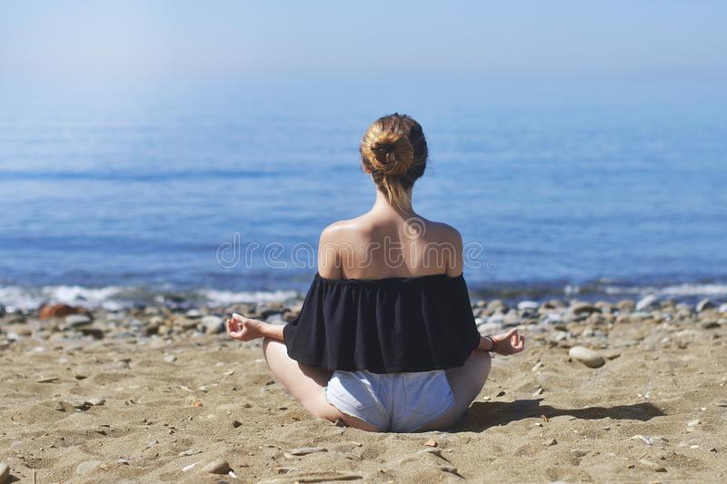 Young woman makes meditation in lotus pose on sea / ocean beach, harmony and contemplation. Beautiful girl practicing yoga at sea stock photography
