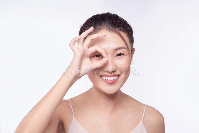 Young woman, makes ok sign, covers her eye.  royalty free stock image